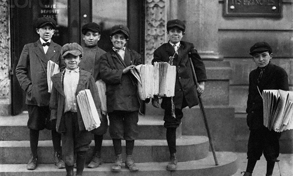 November 1912, Jersey City, New Jersey, USA --- Newspaper boys, one missing a leg, stand on the steps of a bank near a busy trolley junction in Jersey City, New Jersey. --- Image by © CORBIS